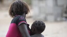 17-летняя мама сидит с ребенком в в южной части Мозамбика